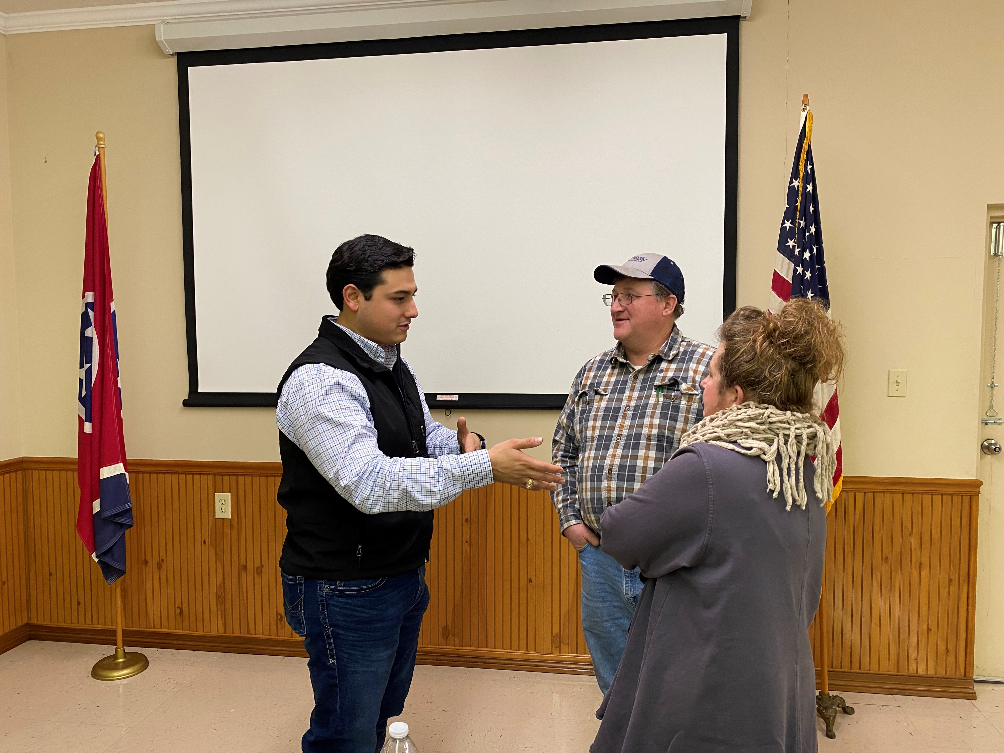 Charley Martinez, Farm Management Economist, talking to couple